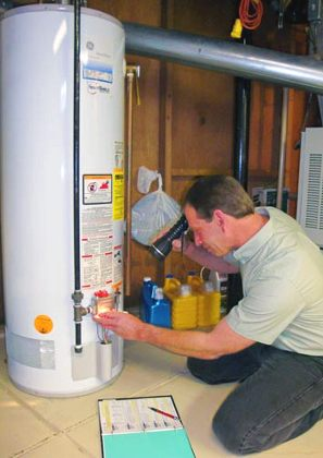 Plumber checking a water heater's intake valves